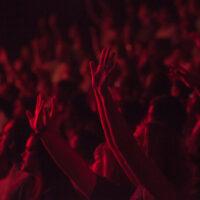 Konsertpublik med händerna i luften i rött ljus